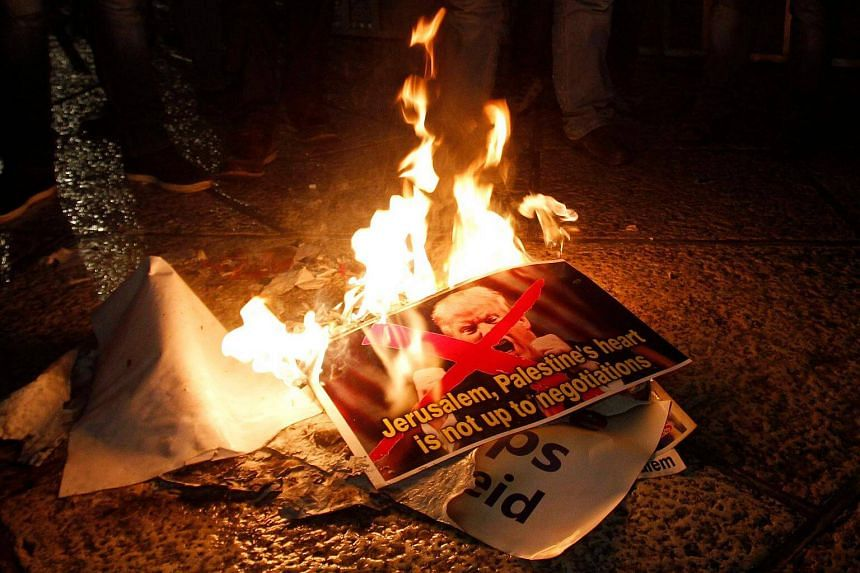 Palestinian demonstrators burning posters of US President Donald Trump, in Bethlehem on Dec 6, 2017.