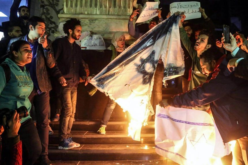 Protestors shouts slogans against US President Donald Trump and burn Israeli flag during a protest in Cairo, Egypt, on Dec 6, 2017.