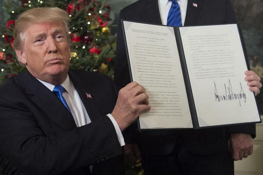 US President Donald Trump holds up a signed memorandum after he recognised the disputed city of Jerusalem as Israel's capital in the White House on Dec 6, 2017.
