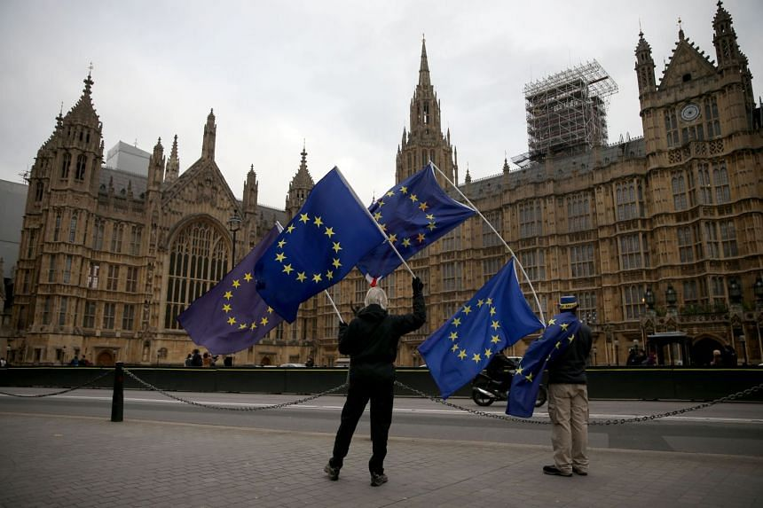 Demonstrators waving the EU flag outside the Houses of Parliament in Westminster, on Dec 5, 2017.
