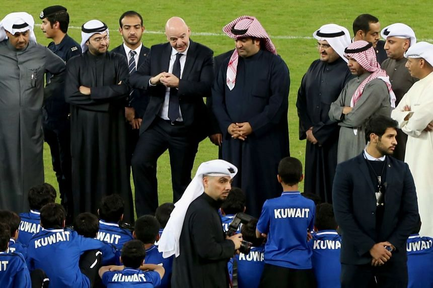 Fifa president Gianni Infantino and Kuwait's Minister of Youth Affairs Khaled Al-Rawdhan (on his left) speaking to Kuwaiti youth during a tour of the Sheikh Jaber Al-Ahmad International Stadium in Kuwait City on Dec 6, 2017.