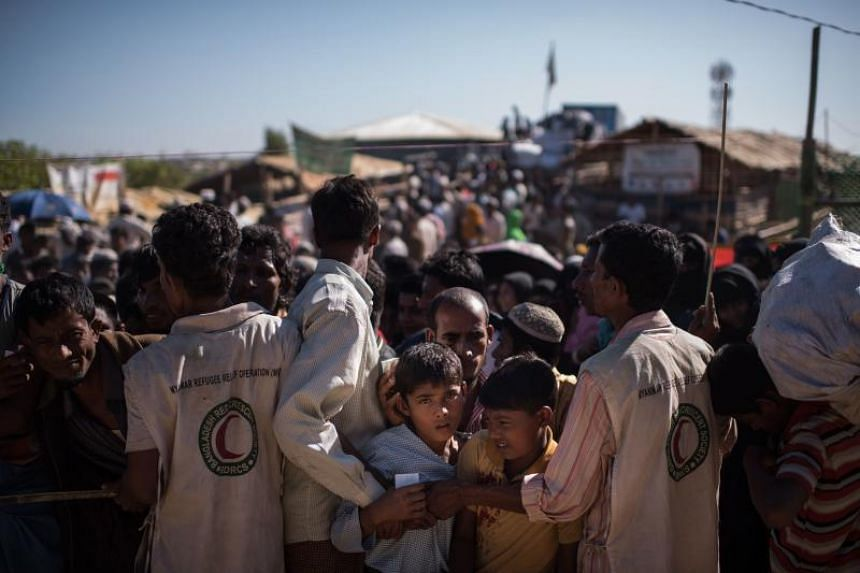 Rohingya Muslim refugees children queue for aid suplies at the Kutupalong refugee camp in Cox's Bazar on December 4, 2017. Rohingya are still fleeing into Bangladesh even after an agreement was signed with Myanmar to repatriate hundreds of thousands