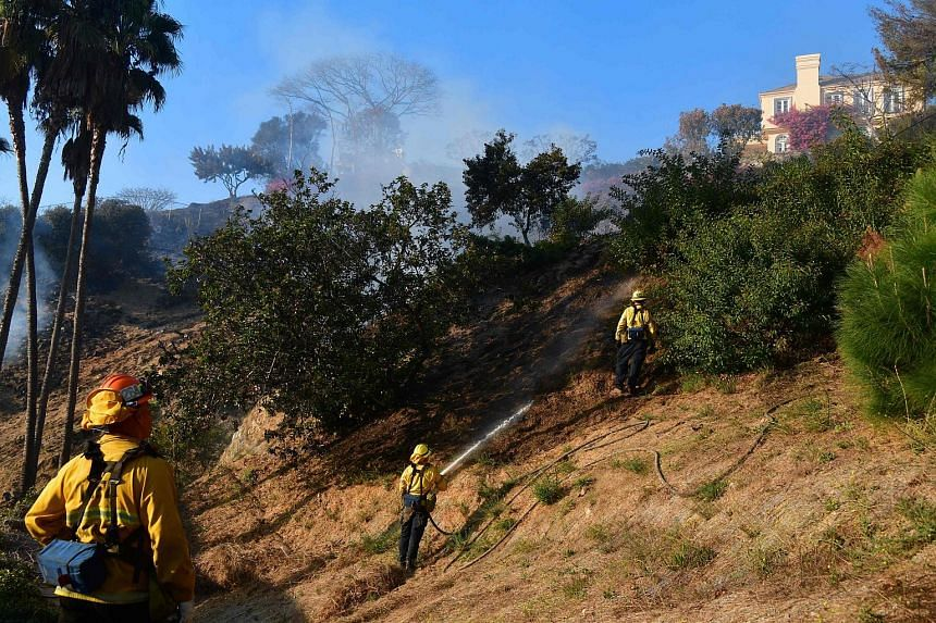 Firefighters put out burning embers on a hillside beneath homes in Bel-Air, Los Angeles on Dec 6, 2017.