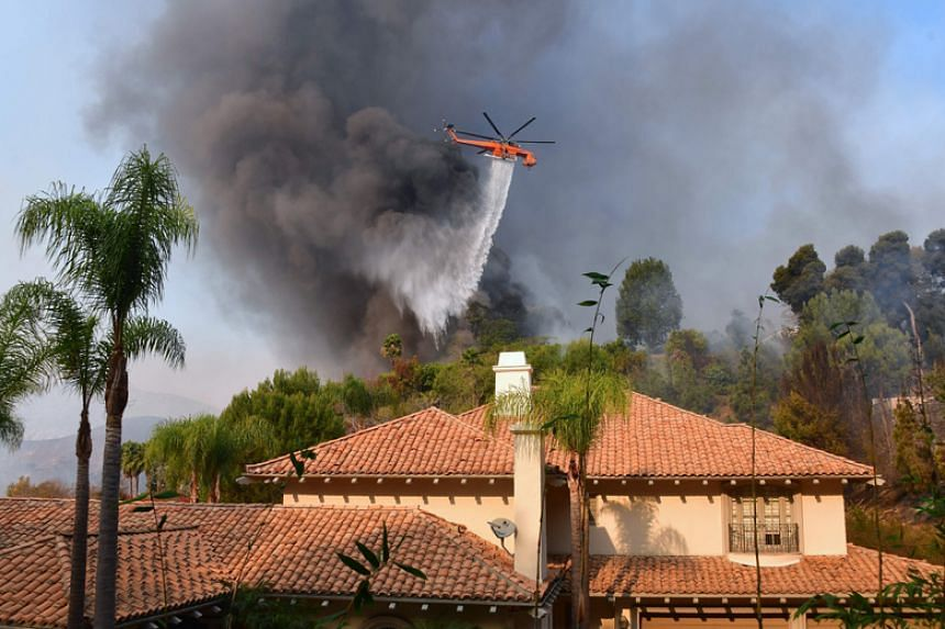 A helicopter drops water over a house on the hilltop in the affluent Los Angeles neighbourhood of Bel-Air on Dec 6, 2017.