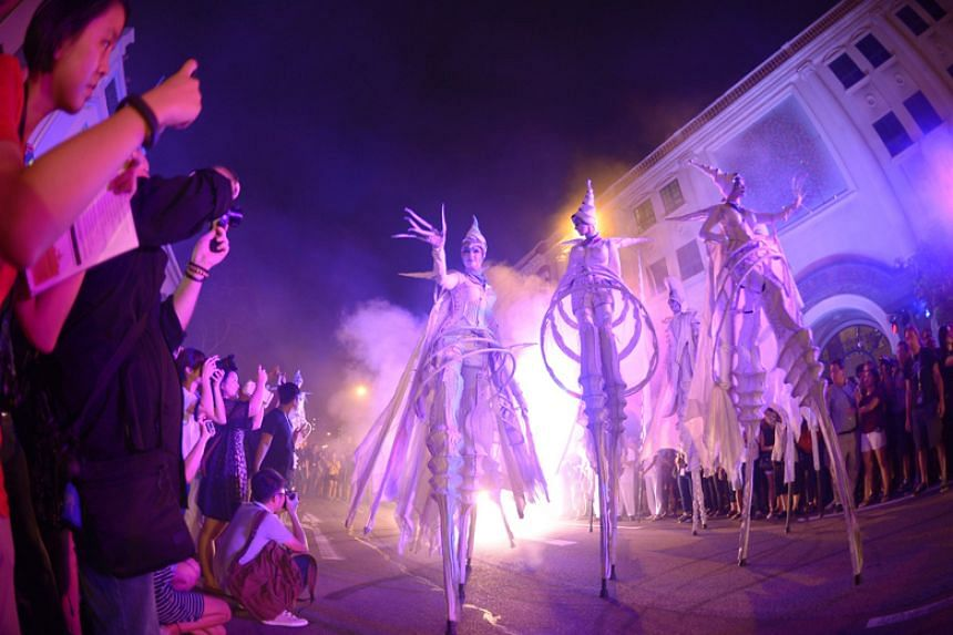 Silver-suited stilt-walkers from Dutch street theatre group Close-Act parade down Armenian Street on Aug 26, 2016 during the ninth Singapore Night Festival.