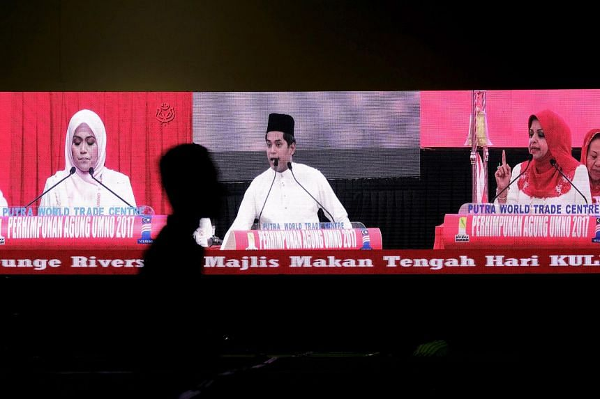 From right: Umno Women's chief Shahrizat Abdul Jalil, Youth chief Khairy Jamaluddin and Puteri chief Mas Ermieyati giving their policy speeches yesterday as shown on a giant screen.