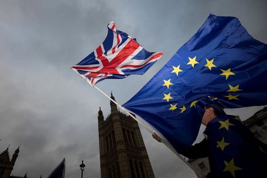 An anti-Brexit protester waves EU and British flags outside the Houses of Parliament in London, Dec 5, 2017.