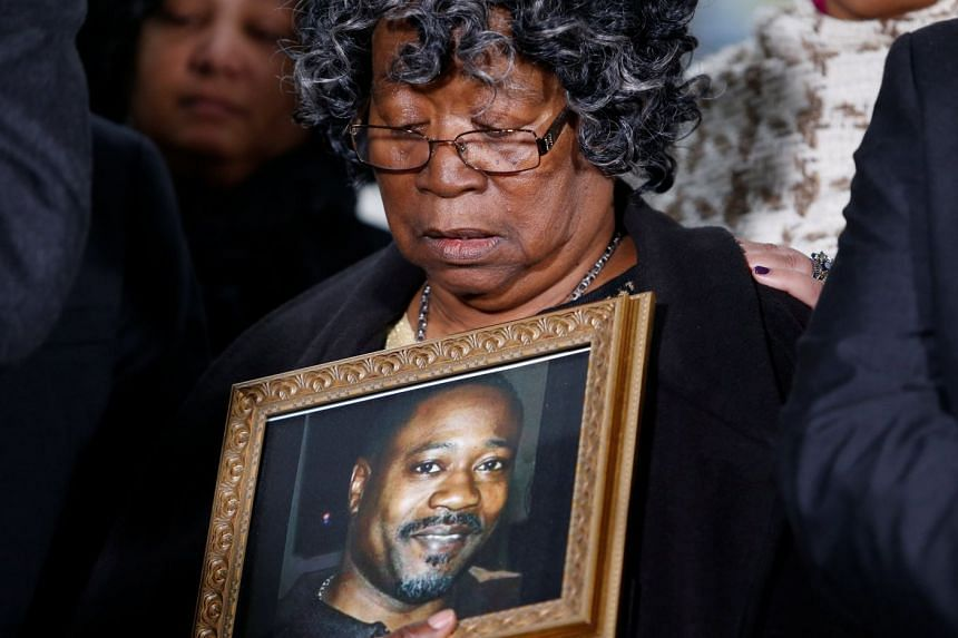 Judy Scott looks over a photo of her son Walter Scott during a news conference, Dec 7, 2017.