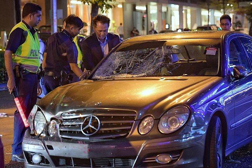 The driver of the Mercedes-Benz, accompanied by police officers, at his car after the accident outside Amara Hotel yesterday. Passers-by helping pedestrians who were injured during the accident, which happened at about 6.30pm, during rush hour.