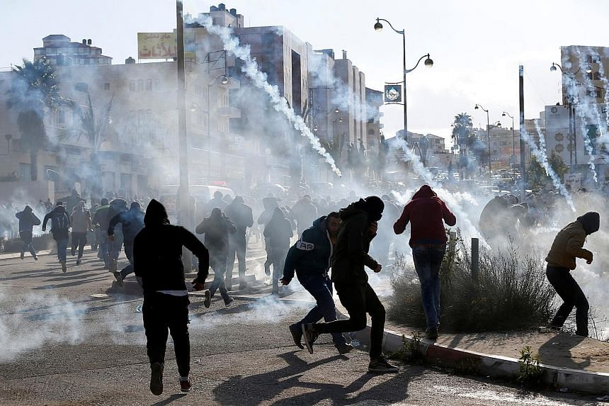 Above: Palestinian protesters running from tear gas fired by Israeli troops yesterday during clashes at a protest against the US' move to recognise Jerusalem as the Israeli capital, near the West Bank city of Ramallah. Below: Mr Trump holding the pro