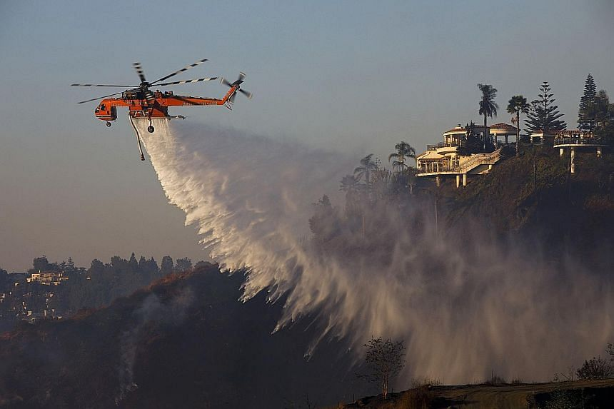 A firefighting helicopter dropping water over the Bel-Air neighbourhood of Los Angeles, California, on Wednesday in an effort to douse a blaze. The raging wildfires have threatened multimillion-dollar mansions with blazes that have already forced mor