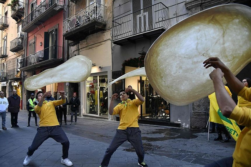 "Members of the Pizzaioli Acrobats Coldiretti twirling pizza to celebrate the Unesco decision to make Neapolitan pizzaiuolo an ""intangible heritage"". The custom goes beyond the handling of dough to include songs and stories that have turned pizza-maki"