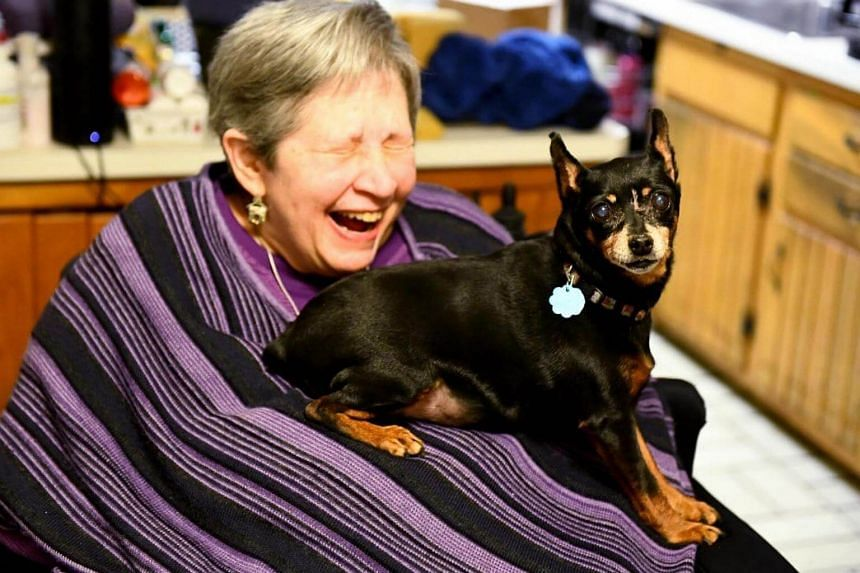 Harriet Fridkin, laughs after her dog, Gracie, crawled on her.