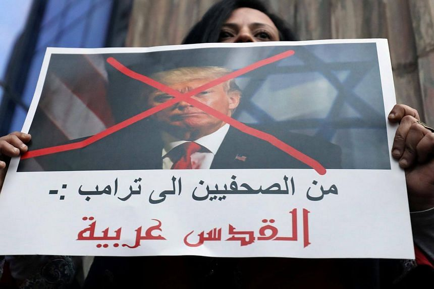 A protester holds a poster of US President Donald Trump that reads, 'From the journalists to Trump: Jerusalem is Arab' in front of the Syndicate of Journalists in Cairo, Egypt, on Dec 7, 2017.