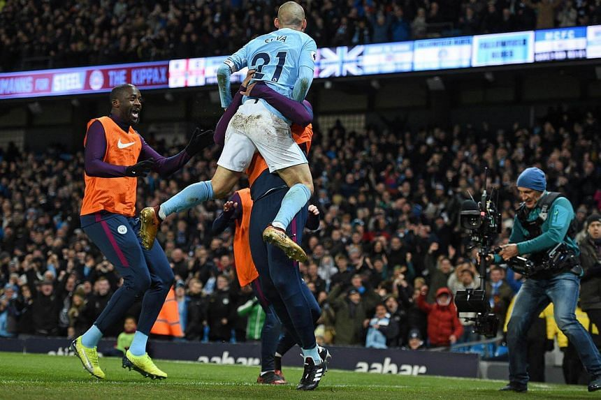 Manchester City's midfielder David Silva leaps into the arms of Manchester City's Belgian captain Vincent Kompany, on Dec 3.