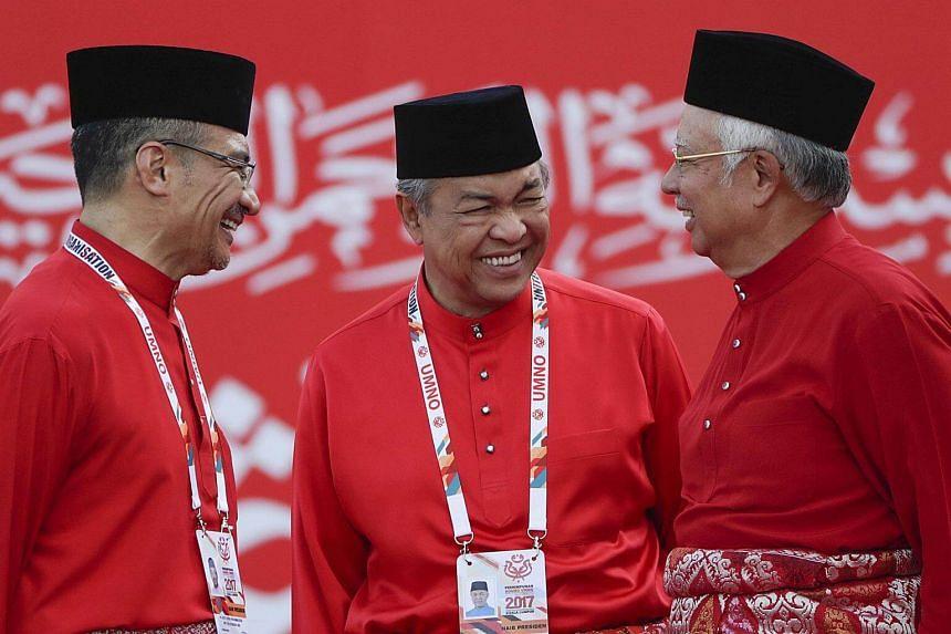 Umno party president Najib Razak (right) with his deputy Zahid Hamidi (centre) and Hishamuddin Hussein (left) at the opening ceremony of the Umno 70th General Assembly 2017.