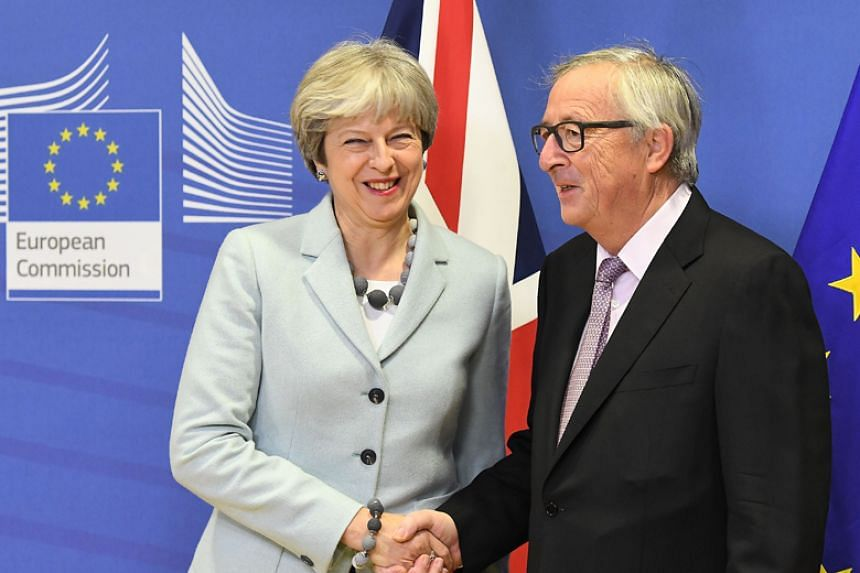 British Prime Minister Theresa May is welcomed by European Commission Jean-Claude Juncker at European Commission in Brussels on Dec 8, 2017.