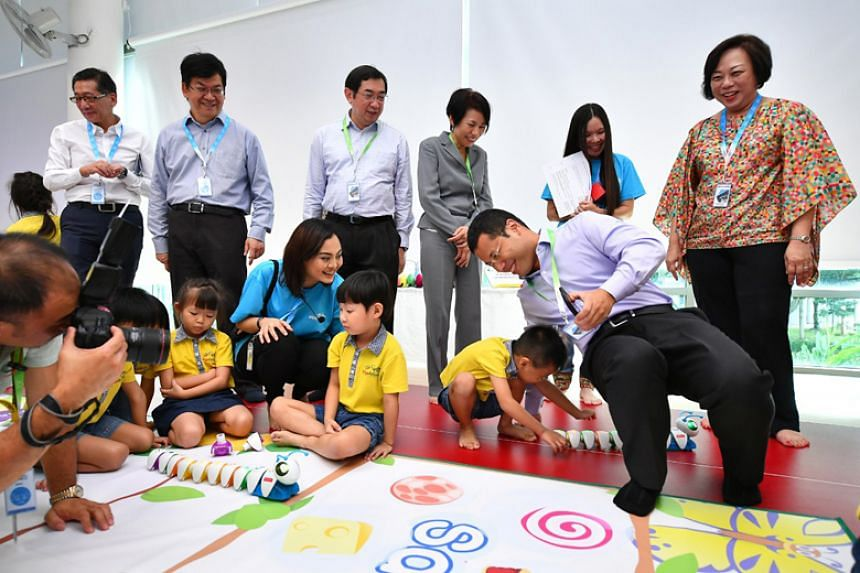 Minister for Social and Family Development and Second Minister for National Development Desmond Lee interacts with children playing with Code-A-Pillar, a coding toy for children, at Skool4Kidz Campus @ Yishun.