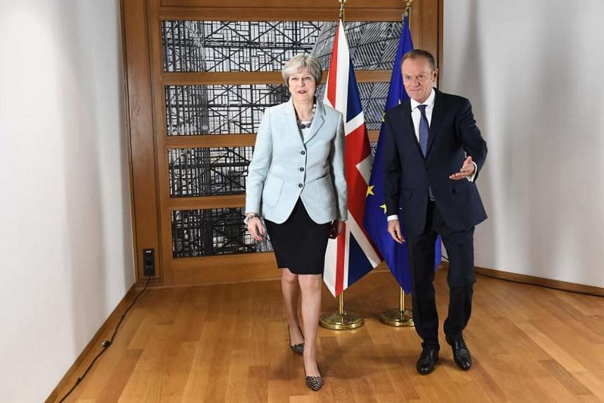 British Prime Minister Theresa May and European Council President Donald Tusk leave after posing for photographers at the European Council in Brussels on Dec 8, 2017.