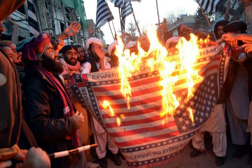 Supporters of Islamic political party Jamiat Ulma-e-Islam burn a mock US flag during protests in Quetta, Pakistan on Dec 8, 2017.