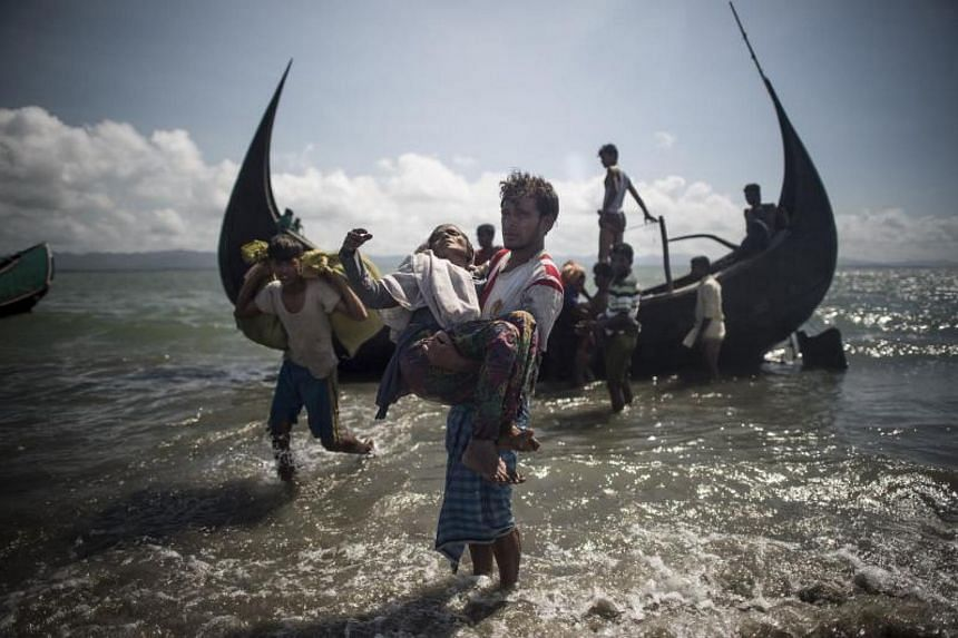 A Bangladeshi man helps Rohingya Muslim refugees to disembark from a boat on the Bangladeshi shoreline of the Naf river after crossing the border from Myanmar in Teknaf on Sept 30, 2017.