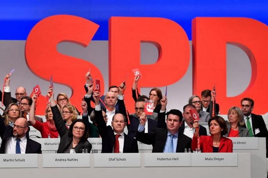Board members of Germany's Social Democratic Party (SPD) vote to kick off exploratory talks with Chancellor Angela Merkel's conservatives during the SPD's party congress in Berlin on Dec 7, 2017.