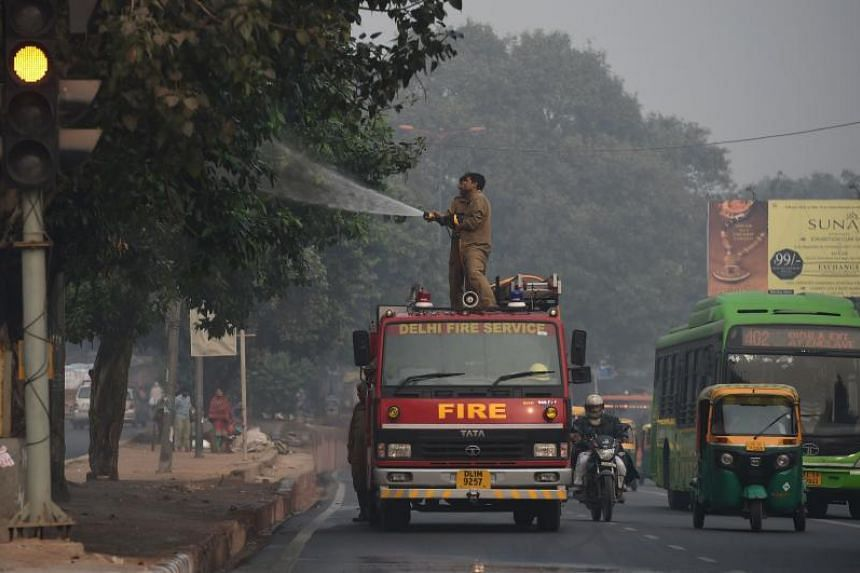 Indian firefighters spray water onto trees at the roadside in a bid to curb air pollution by combating accumulated dust in New Delhi on Nov 16, 2017.