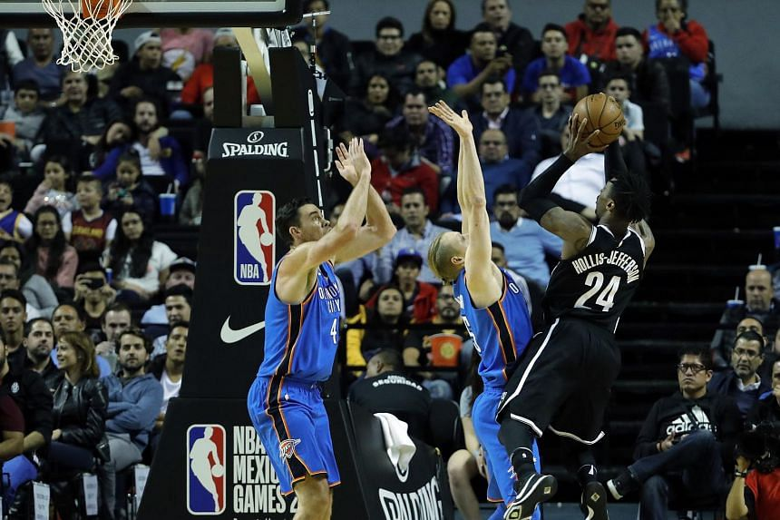 Brooklyn Nets forward Rondae Hollis-Jefferson (right) shoots over two Oklahoma City Thunder defenders during the game.