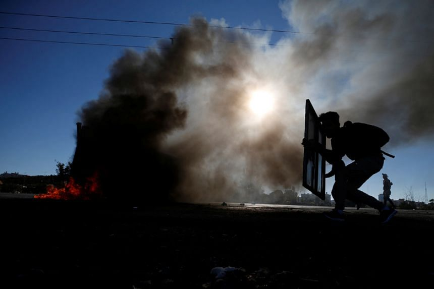 """A Palestinian protester takes cover during clashes with Israeli troops as Palestinians call for a """"Day of Rage"""" in response to US President Donald Trump's recognition of Jerusalem as Israel's capital, near the Jewish settlement of Beit El on Dec 8, 2"""