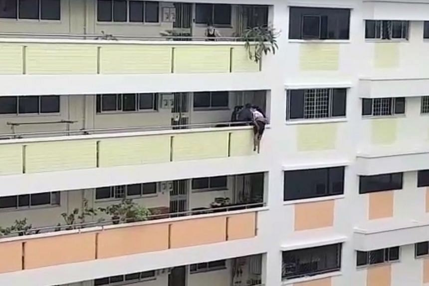 (From left) The maid climbs out of the window of the room; she walks along the ledge towards the tenant in the corridor outside the unit; the tenant and a police officer grab the maid and try to pull her over the railings; and she is finally pulled t