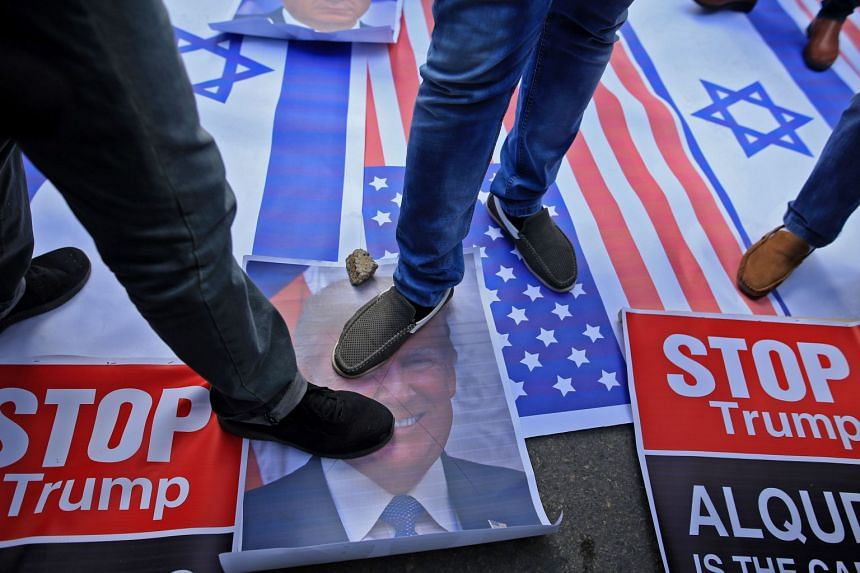 Palestinian protesters step on US and Israeli flags and on a portrait of US President Donald Trump in Gaza City.