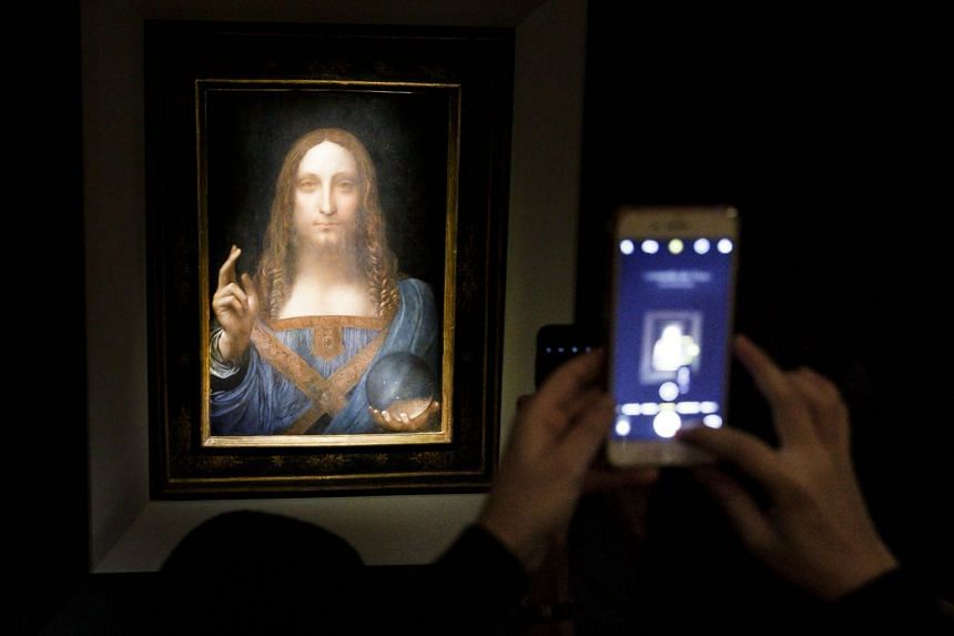 People take pictures of the painting Salvator Mundi during a public preview ahead of the auction.