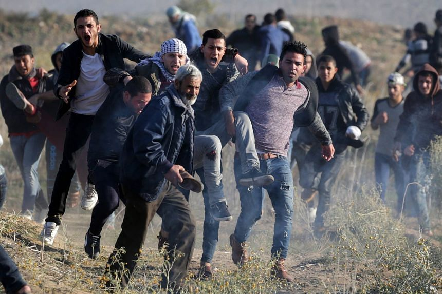 Palestinian protesters carry a wounded man during clashes along the border between Israel and Gaza, Dec 8, 2017.