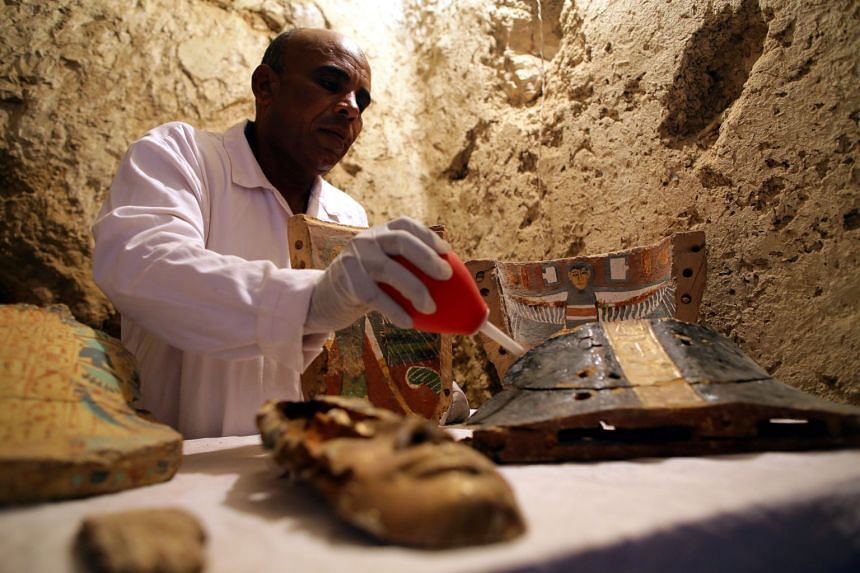 An Egyptian archaeologist works on restoring items found at Draa Abul Naga necropolis.