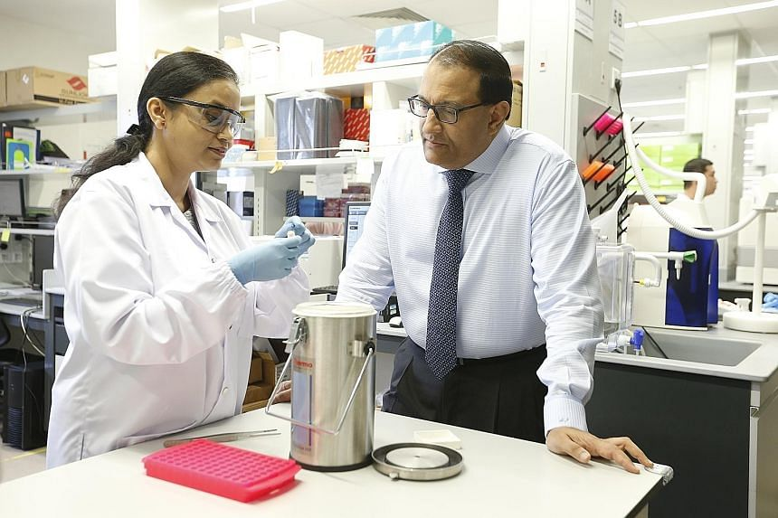 Dr Lakshmi Ramakrishna explaining to Minister for Trade and Industry (Industry) S. Iswaran how patient samples preserved in liquid nitrogen canisters are the start point for research projects at a lab in SingHealth Academia, located in SGH.