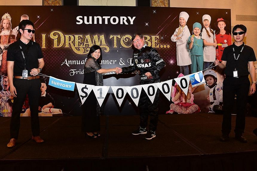The Straits Times School Pocket Money Fund's general manager Tan Bee Heong receiving a donation of $100,000 from Mr Kazuhiro Saito, chief executive of Suntory Beverage and Food Asia, at the company's dinner and dance yesterday. The sum was raised thr
