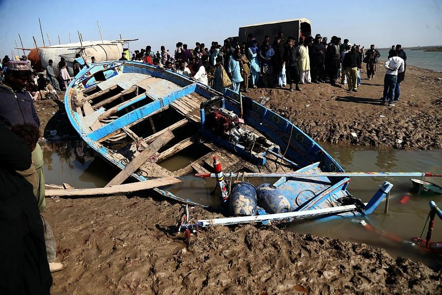 Devotees gathered around a boat that capsized on Thursday while carrying pilgrims to a Sufi Muslim shrine in Pakistan's Sindh province, near the ancient city of Thatta. Media reports said at least 26 people were killed, including women and children,