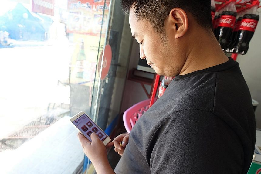Grocery shop owner Wai Shan Phyo checking his phone banking application on his mobile phone while in his shop. But the 28-year-old limits himself to items costing no more than 15,000 kyat, in case his orders never arrive. Above: Two women leaving a K