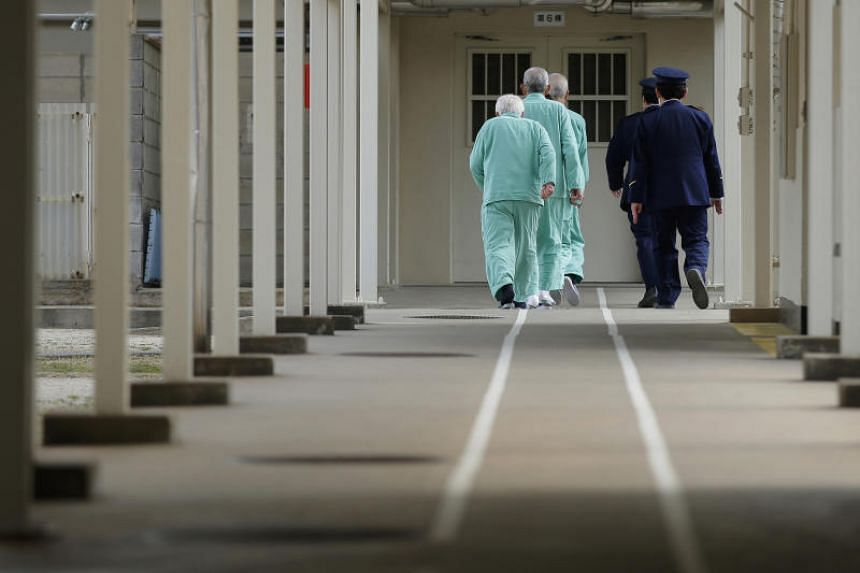 Prison guards escort inmates walking in single file along a marked pathway at Sasebo Prison in Sasebo, Nagasaki Prefecture, Japan.