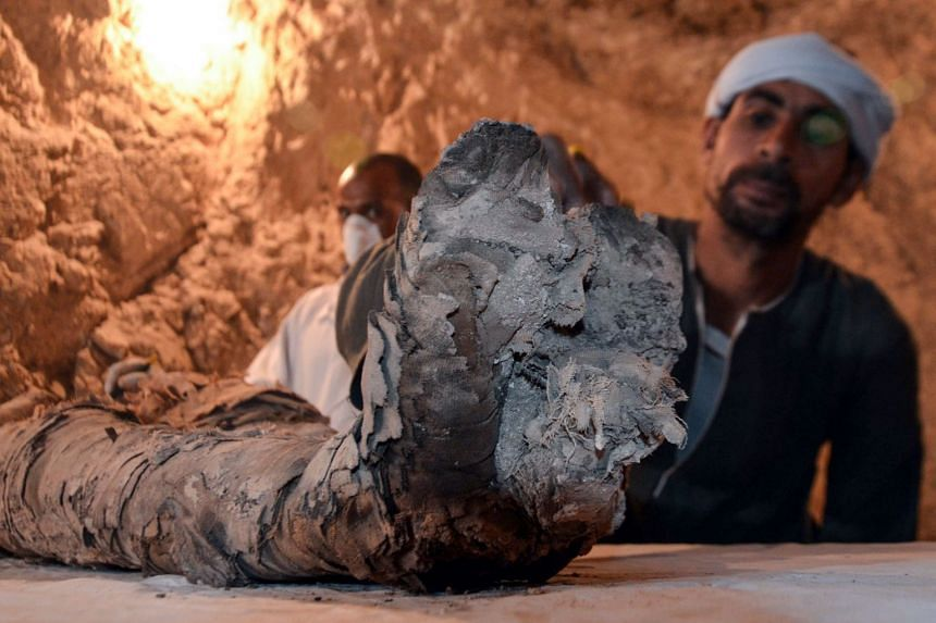 Egyptian archaeological technicians restore a mummy wrapped in linen, found at Draa Abul Naga necropolis.
