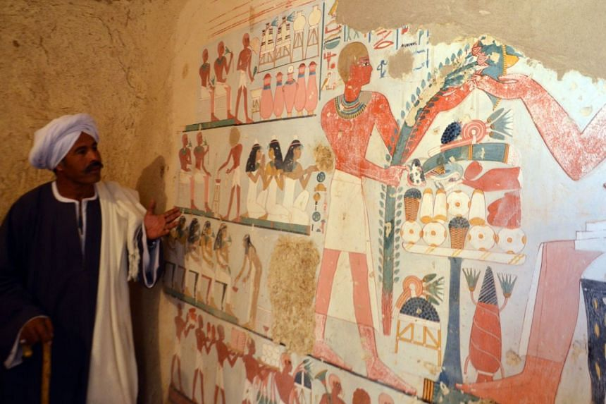An Egyptian labourer stands next to an ancient Egyptian mural found at Draa Abul Naga necropolis.