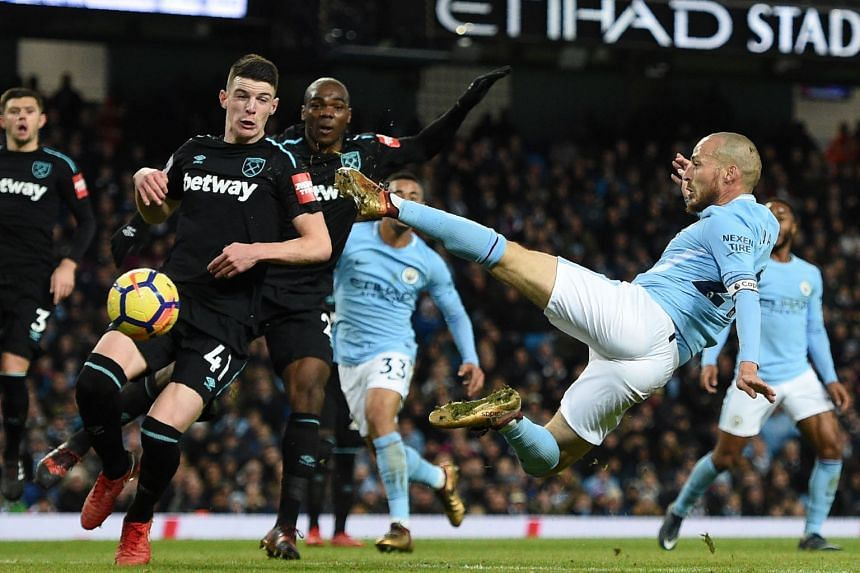 Manchester City's Spanish midfielder David Silva (right) leaps into the air to strike their second goal during the English Premier League football match between Manchester City and West Ham United, on Dec 3, 2017.