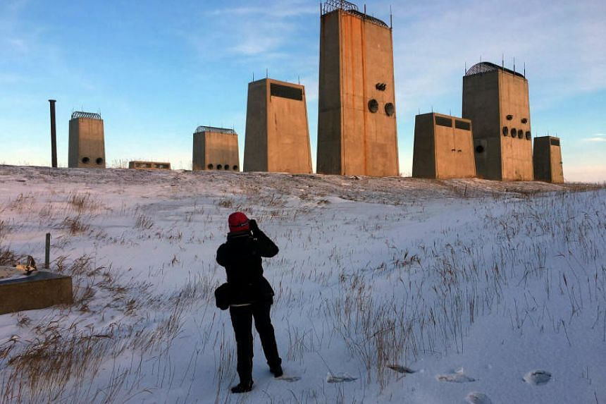 Sim Chi Yin photographs the air intake and exhaust stacks of the underground power station at the Stanley R. Mickelsen Site outside Nekoma, North Dakota, on Nov 17, 2017.