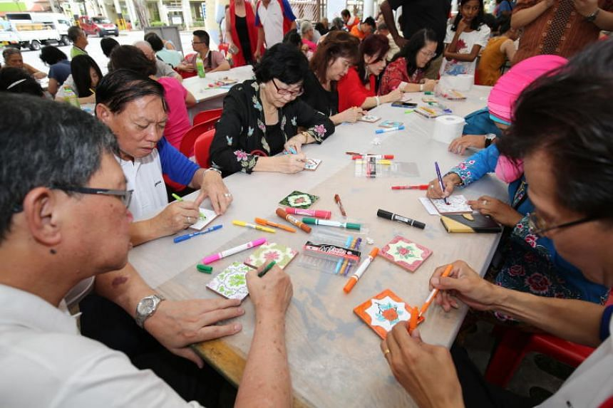Residents paint ceramic tiles during the Peranakan Heritage Trail event on Dec 9. The effort made it to the Singapore Book of Records for most number of Peranakan tiles painted.