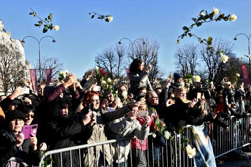 """People throw white roses during a """"popular homage"""" to late French singer Johnny Hallyday as his coffin is driven down the Champs-Elysees avenue on Dec 9, 2017."""