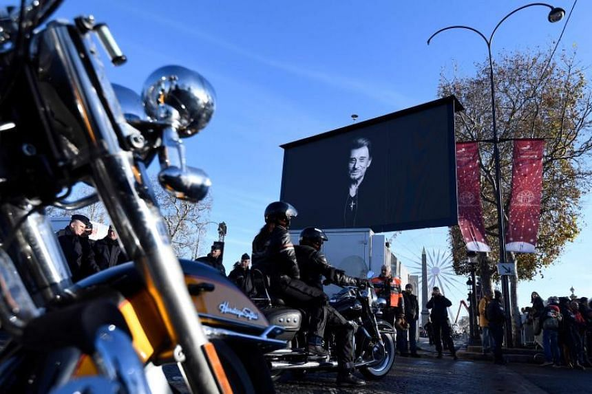 """Motorcyclists ride their bikes during a """"popular homage"""" to late French singer Johnny Hallyday as his coffin is driven down the Champs-Elysees avenue on Dec 9, 2017."""