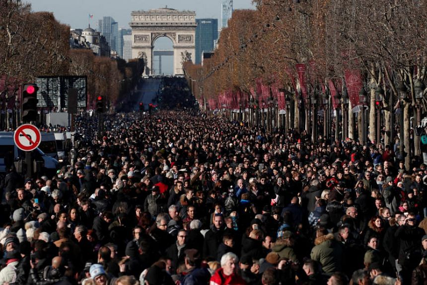 """Fans gather on the Champs Elysees Avenue during a """"popular tribute"""" to the late French singer and actor Johnny Hallyday in Paris."""