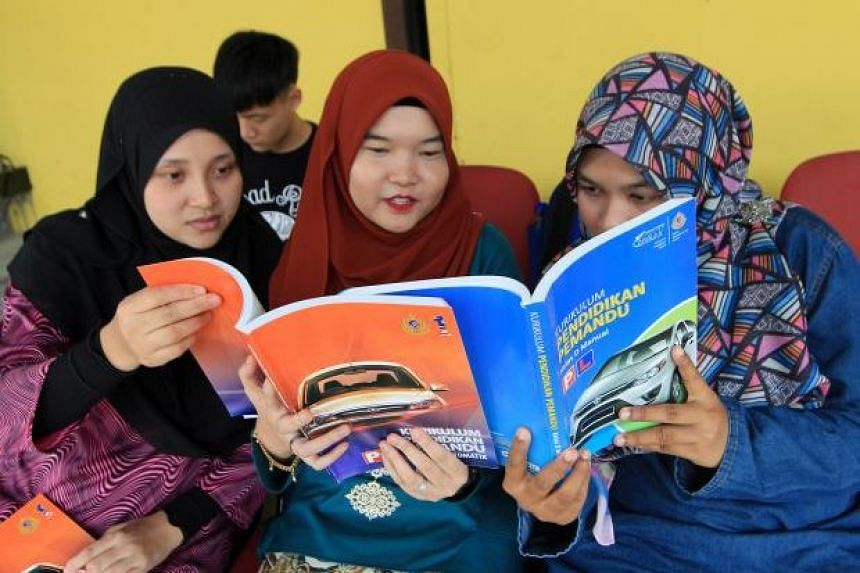 Students at a Petaling Jaya driving school studying the Highway Code to prepare for their learner driver's test.