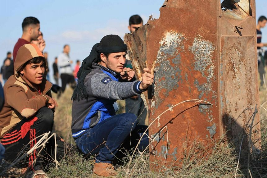 Palestinian protesters clash with Israeli forces on Dec 8, 2017, near the border fence with Israel, east of Gaza City.