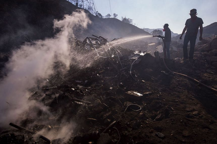 Ranch hands Angel Flores and Anthony Martin hose down smoldering property near stables where 29 horses were killed by the Creek Fire at Rancho Padilla on Dec 6, 2017 near Sylmar, California.